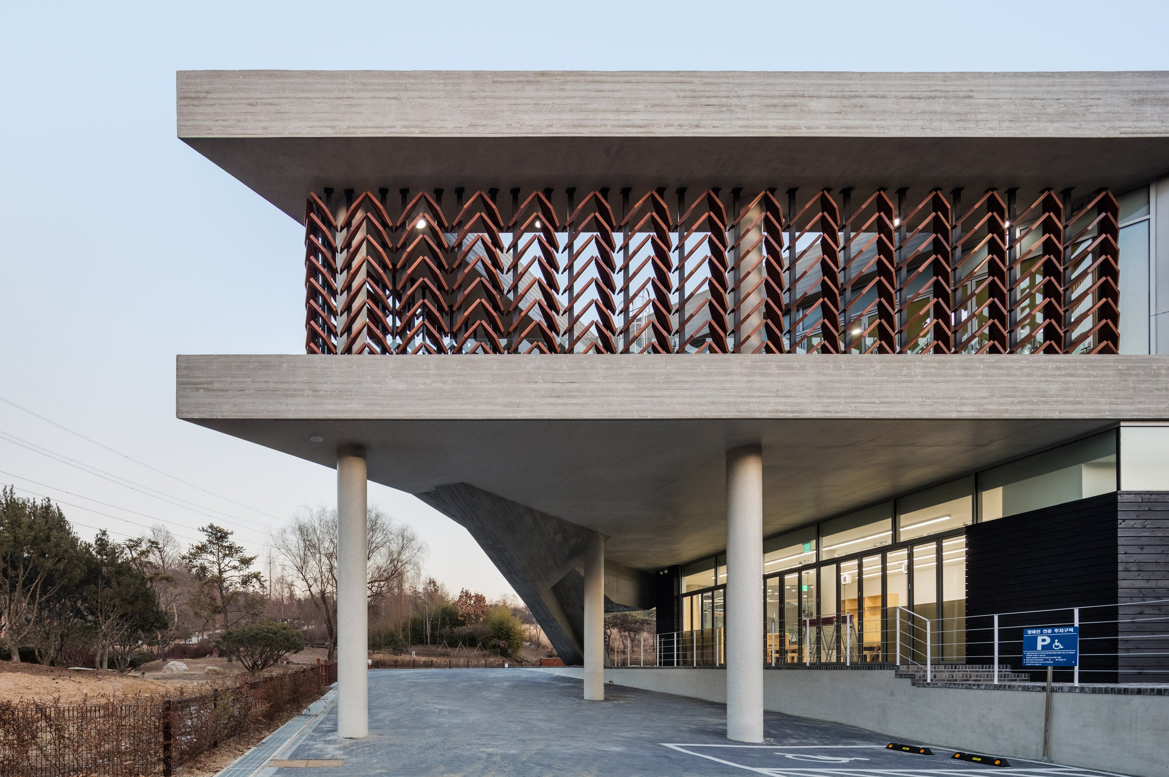 Moveable wooden screens are set into concrete facades of